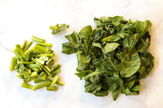showing how to make pad see ew recipe by separating the Chinese broccoli stalks and leaves on a cutting board