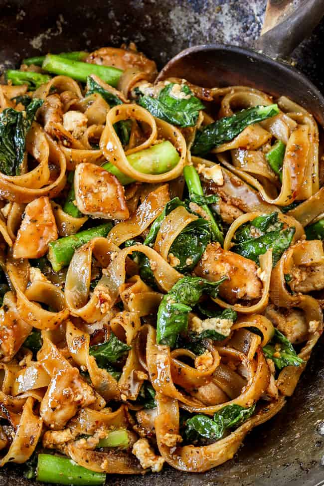 up close of pad see ew noodles in wok smothered in sauce