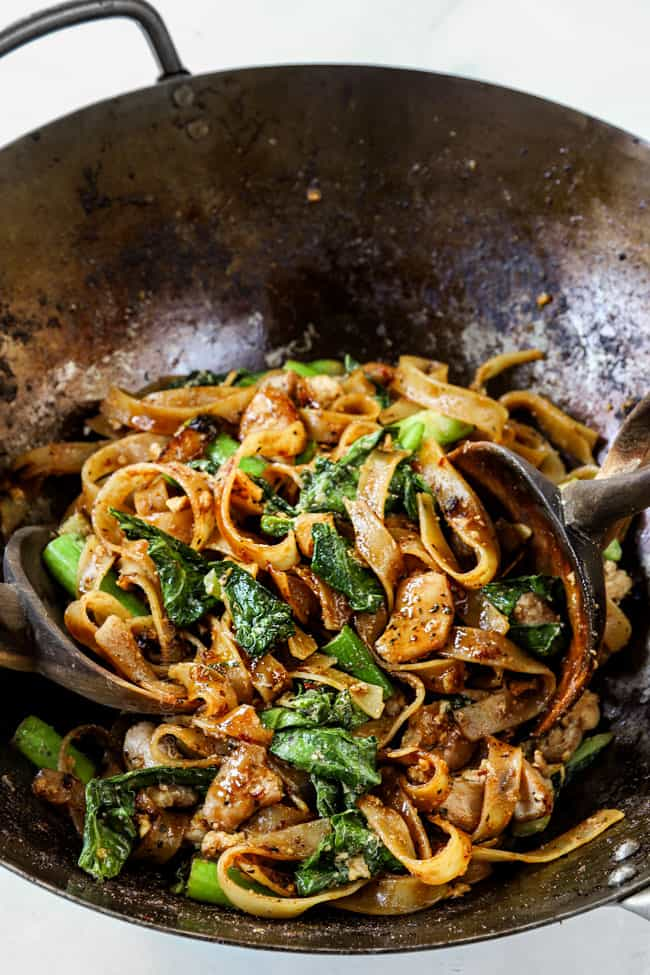 wooden tongs tossing pad see ew noodles together in a wok
