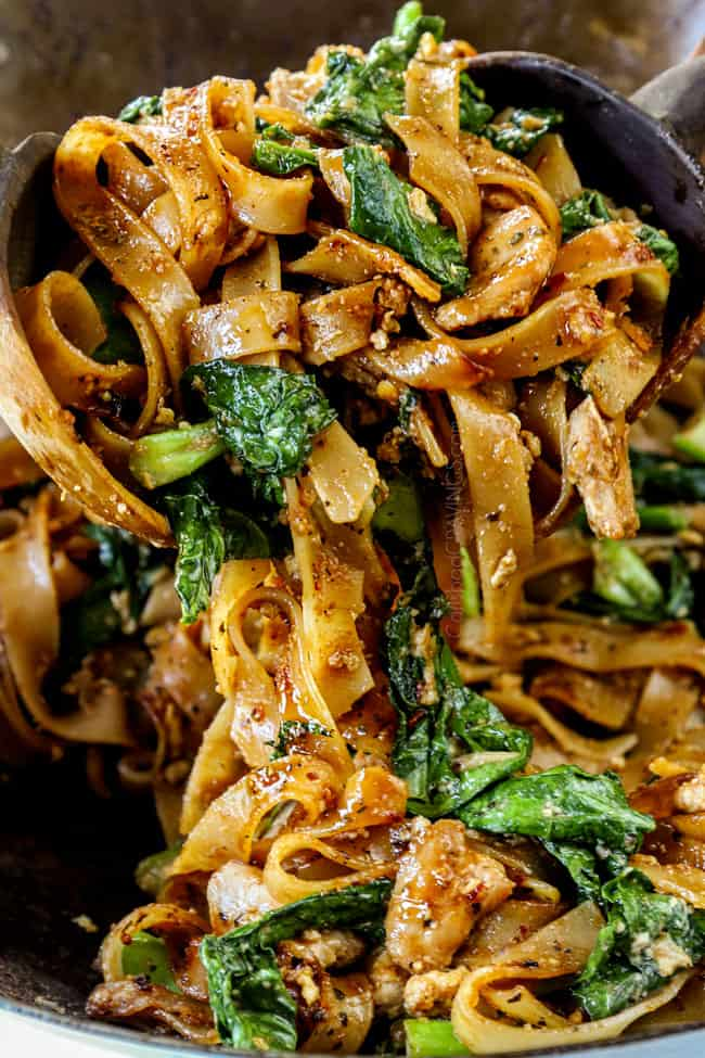 showing how to make pad see ew noodles by tossing chicken, Chinese broccoli and eggs and noodles together with wooden tongs.