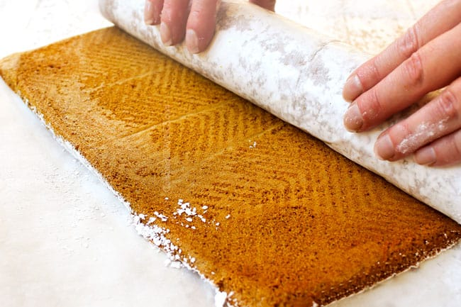 showing how to make a pumpkin roll by rolling up the cake with parchment paper