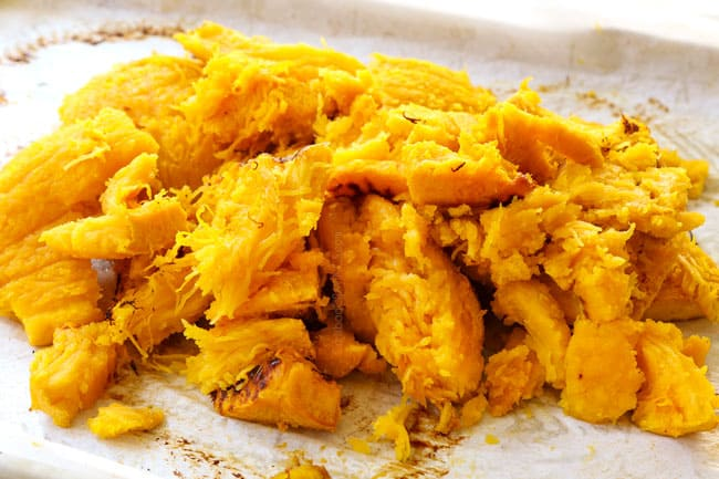 showing how to make pumpkin coconut soup by removing the skin from the pumpkins to reveal the flesh