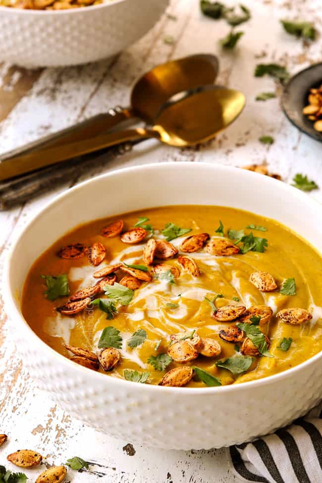 a white bowl of pumpkin coconut soup garnished with pumpkin seeds and cilantro