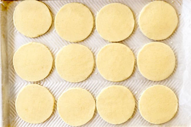 showing how to make sopes recipe by transferring flattened sopes to a parchment paper lined baking sheet