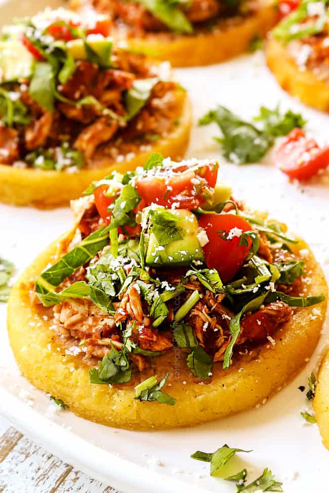 up close of a sope on a white platter with refried beans, shredded chicken, shredded lettuce, tomatoes and avocados