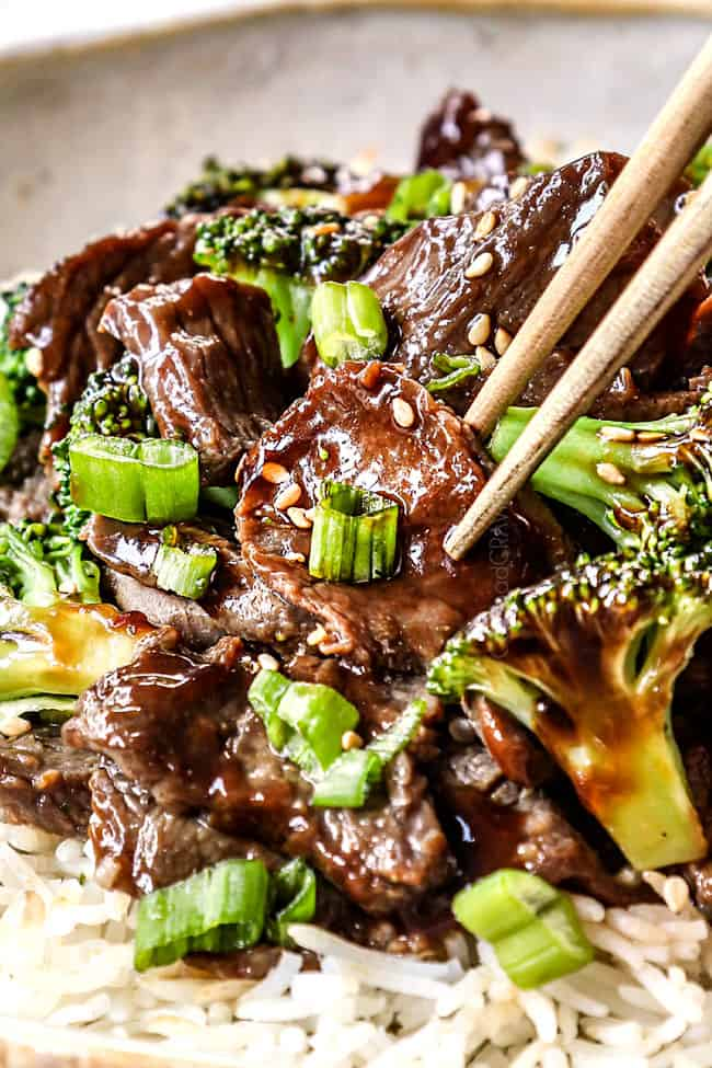 showing how to eat slow cooker crockpot beef and broccoli recipe by picking up a slice of beef with chopsticks