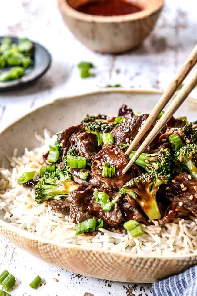 showing how to eat crockpot beef and broccoli by picking beef up with chopsticks served over rice
