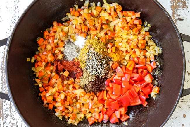 showing how to make lentil curry recipe by adding yellow curry, garlic, ginger, turmeric, coriander, cayenne pepper, cumin to a black pot to bloom the spices