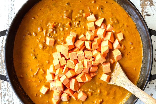 showing how to make lentil curry recipe by stirring in sweet potatoes in a black pot