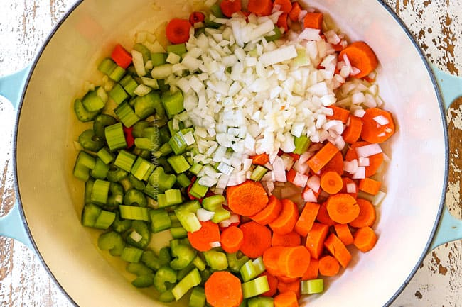 showing how to make leftover turkey rice soup by cooking carrots, onions and celery in a white Dutch oven