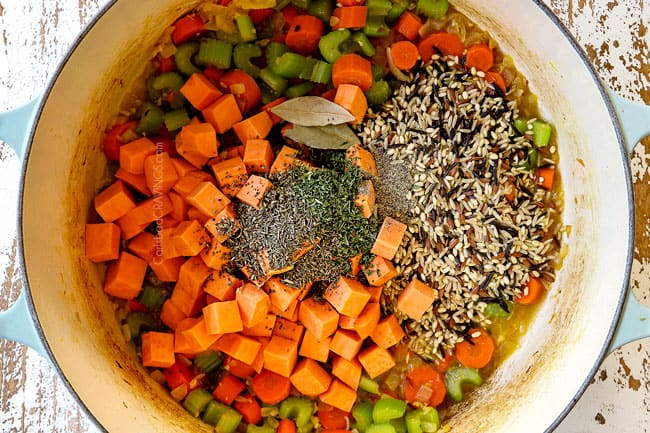 showing how to make leftover turkey rice soup by adding wild rice, sweet potatoes and Italian seasonings to a white Dutch oven