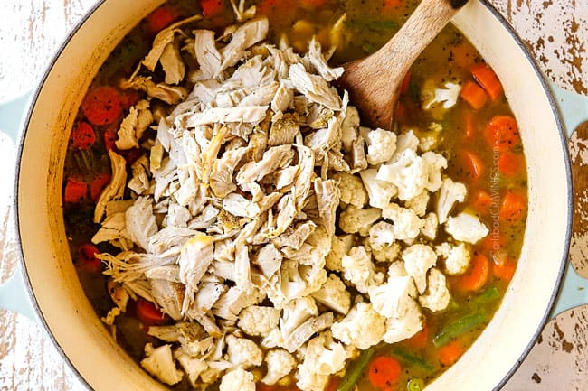 showing how to make leftover turkey rice soup by adding leftover turkey and cauliflower to a white Dutch oven