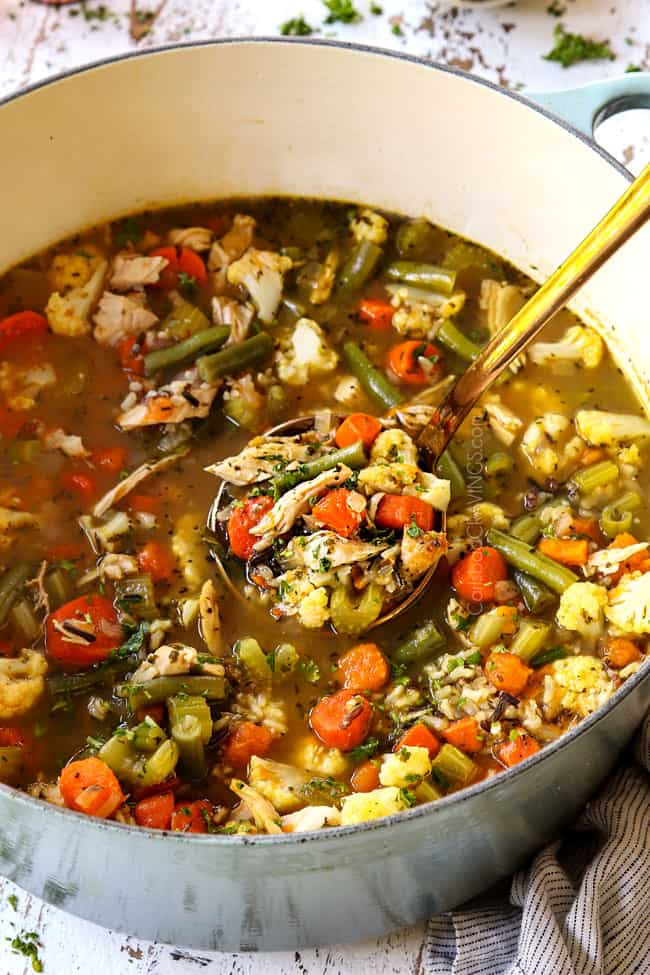 a ladle spooning turkey soup recipe in a big Dutch oven