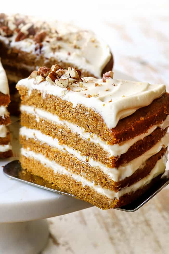 up close of a slice of pumpkin spice cake on cake server being pulled away from the cake stand