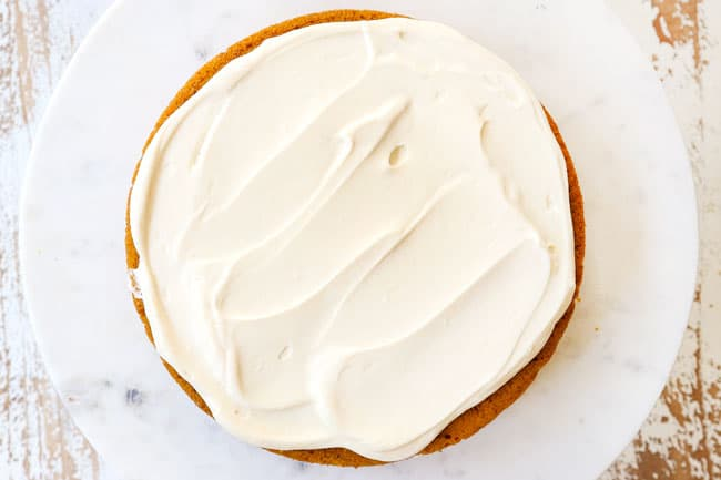 showing how to make pumpkin spice cake by spreading frosting on a cake