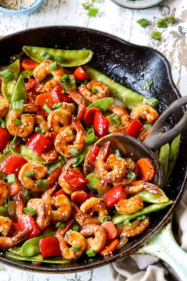 showing how to make shrimp stir fry by combining shrimp and vegetables in a skillet