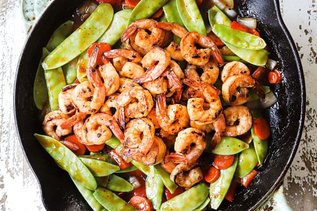 showing how to make shrimp stir fry recipe by adding shrimp to stir fry and combining