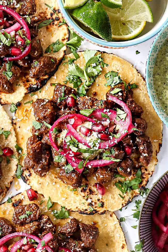 showing how to serve quick pickled red onions by adding to steak tacos