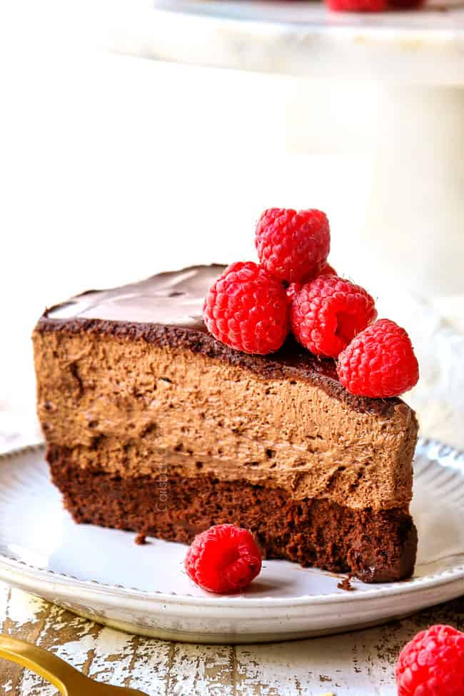 side view of a slice of Chocolate Mousse Cake on a white plate