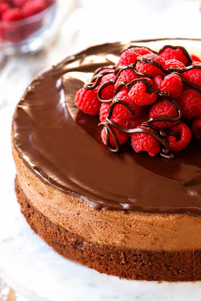 showing how to make Chocolate Mousse Cake recipe by garnishing with raspberries