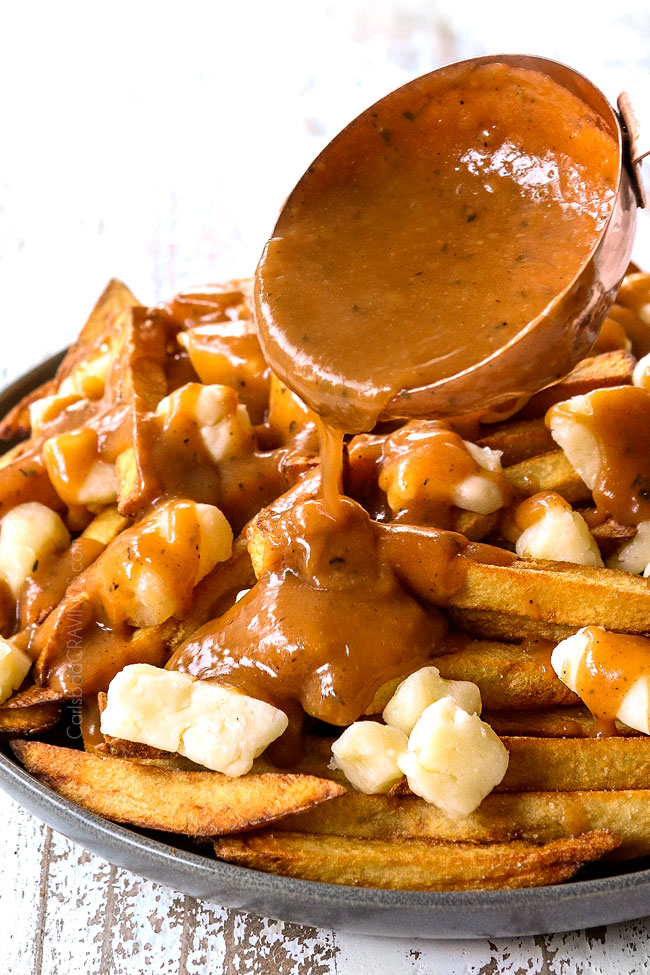 showing how to make poutine by drizzling with gravy with a ladle