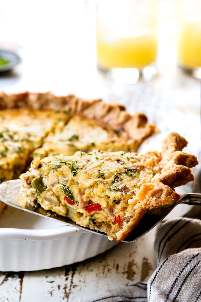 showing how moist ham and quiche recipe is by holding up a slice