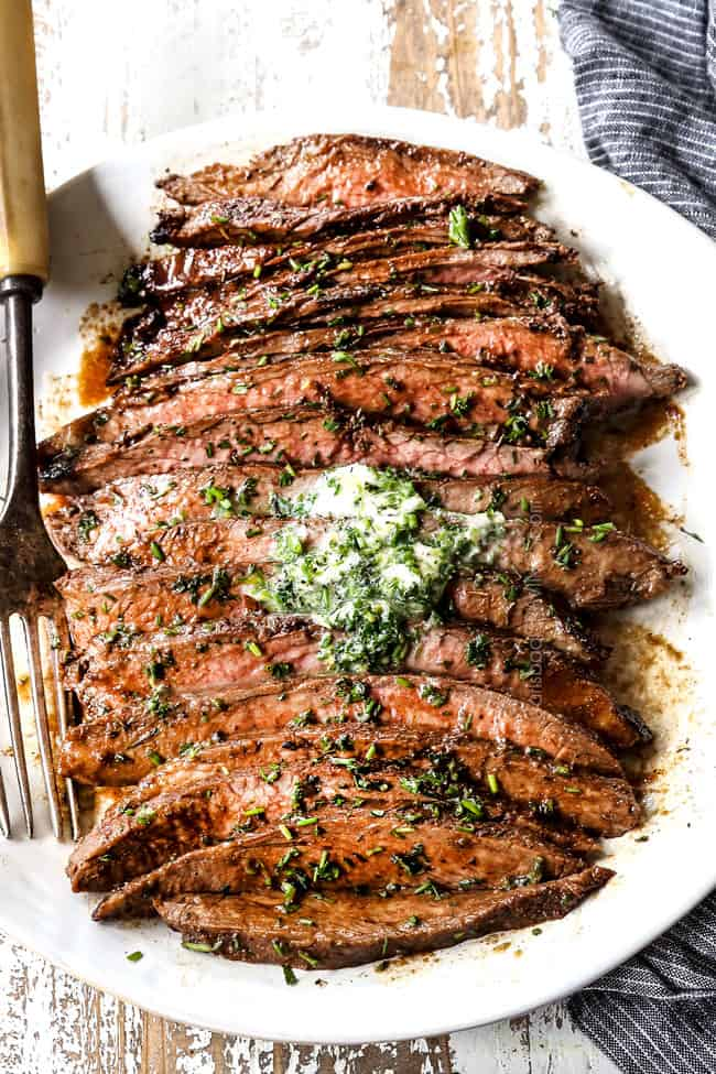 top view of London Broil on a white platter with herb butter