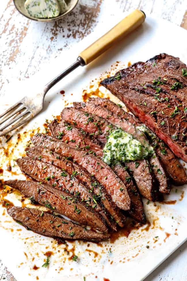London Broil recipe on a white cutting board with herb butter