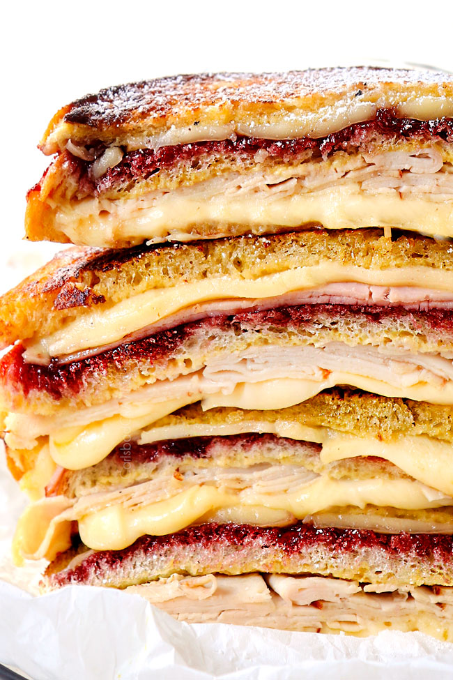 up close of a stack of Monte Cristo sandwiches showing how cheesy they are