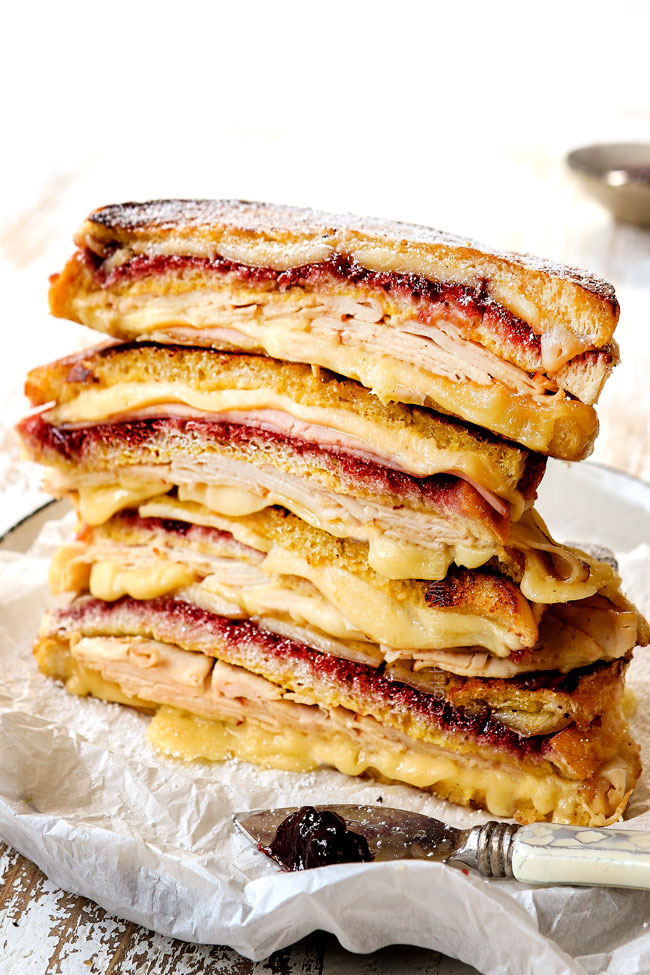 a stack of sliced Monte Cristo sandwiches with ham, turkey, Swiss cheese