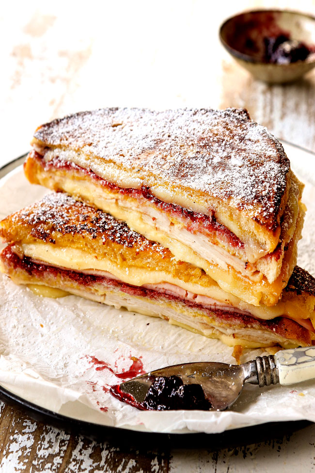 Monte Cristo recipe sliced in half on a plate dusted with powdered sugar