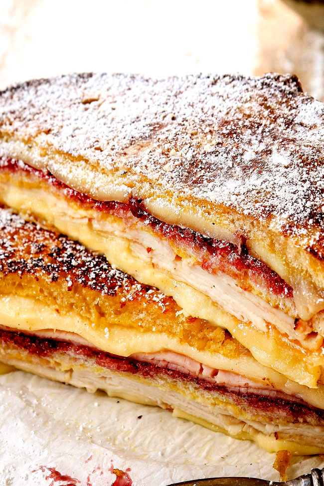 showing how to make Monte Cristo recipe by dusting with powdered sugar and serving with raspberry jam