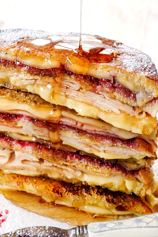 showing how to make Monte Cristo sandwich recipe by drizzling a stack of Monte Cristos with syrup