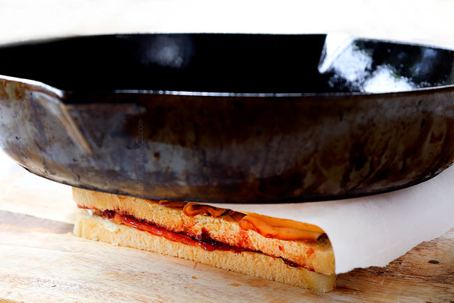 showing how to make Monte Cristo sandwich recipe by pressing the sandwich with a cast iron skillet