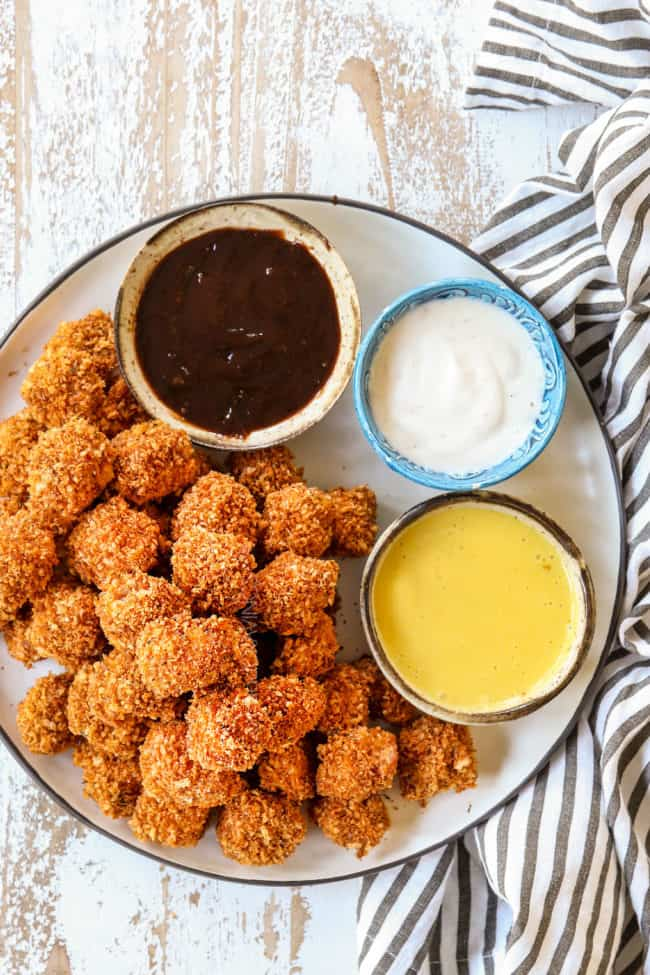top view of homemade chicken nuggets on a white plate served with BBQ sauce, ranch and honey mustard dip