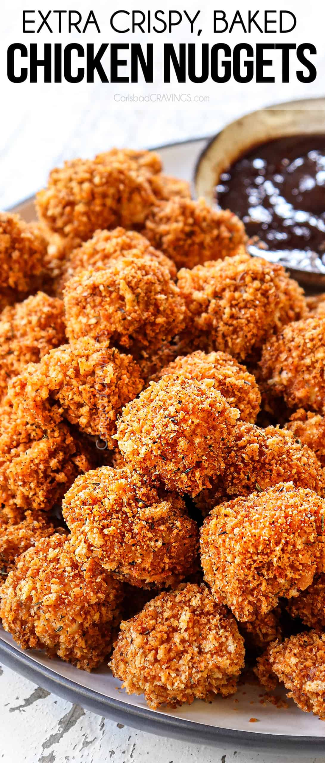 up close view of baked chicken nuggets stacked on a plate showing how crispy they are