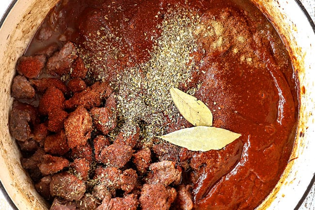 showing how to make Chile Colorado recipe by adding chile sauce, beef, oregano, cumin, bay leaves and beef broth to Dutch oven