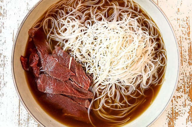 showing how to make pho by adding beef and noodles to a bowl with beef broth