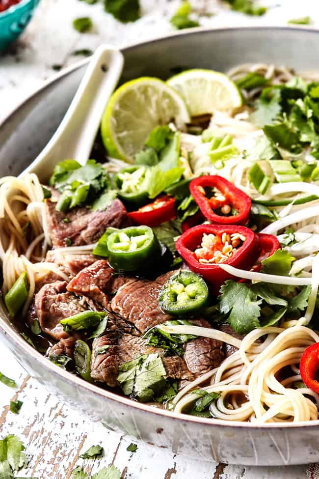 pho recipe with thinly sliced beef  garnished with chili peppers, bean sprouts and cilantro