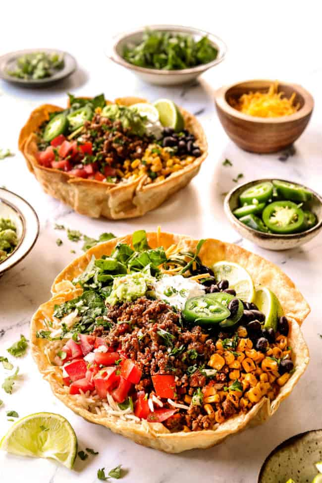 taco bowl recipe in taco bowl shells with ground beef, corn, black beans, tomatoes, lettuce and sour cream and guacamole