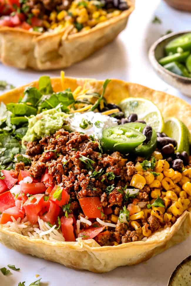 up close of taco bowl recipe with taco bowl shells filled with ground beef, corn, tomatoes and black beans