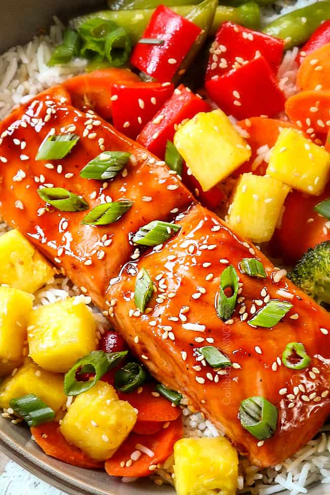 up close of teriyaki glazed salmon garnished with green onions and sesame seeds