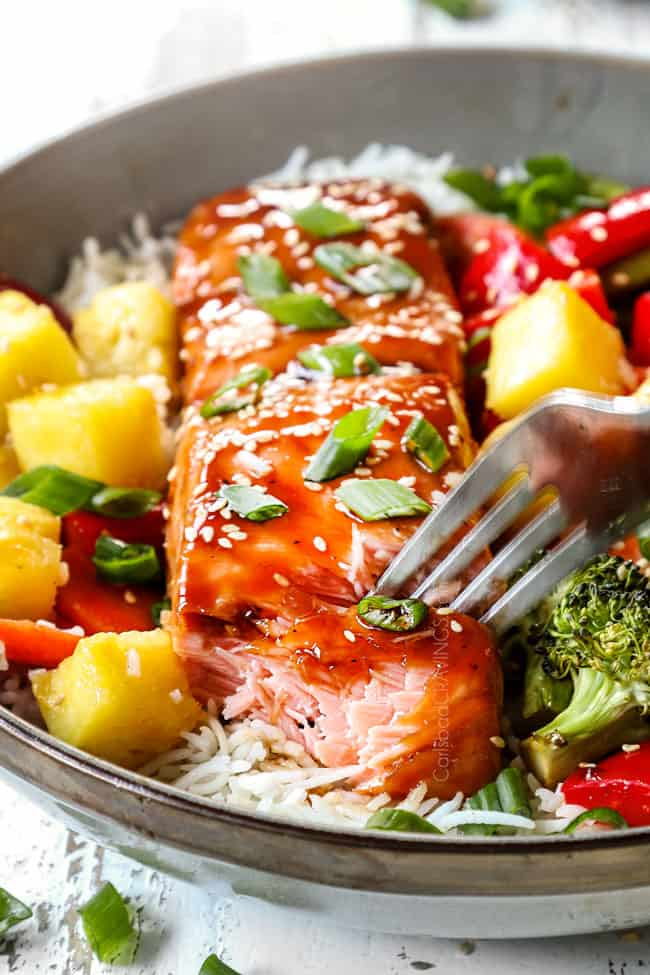 baked teriyaki salmon recipe in a bowl with a fork taking a bite showing how juicy the salmon is