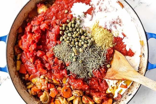 showing how to make chicken cacciatore recipe by adding crushed tomatoes, diced tomatoes, Italian seasonings and heavy cream to the pot