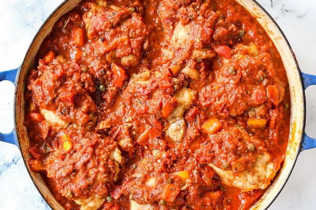 showing how to make chicken cacciatore recipe by adding chicken back to the pot and covering with sauce