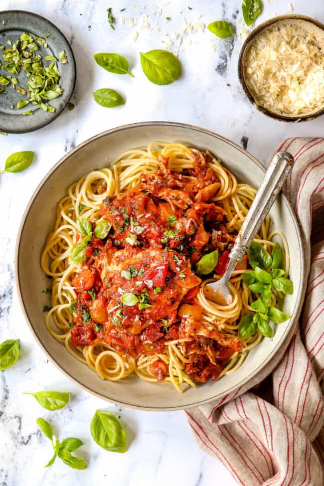 top view of chicken cacciatore served over spaghetti in a bowl