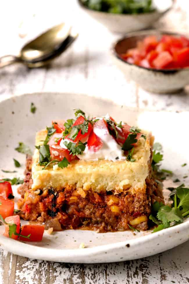 a slice of tamale pie on a plate topped with tomatoes, sour cream and cilantro