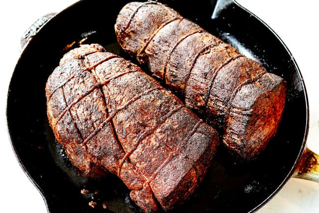 showing how to cook beef tenderloin by searing beef tenderloin roasts on all sides in a cast iron skillet