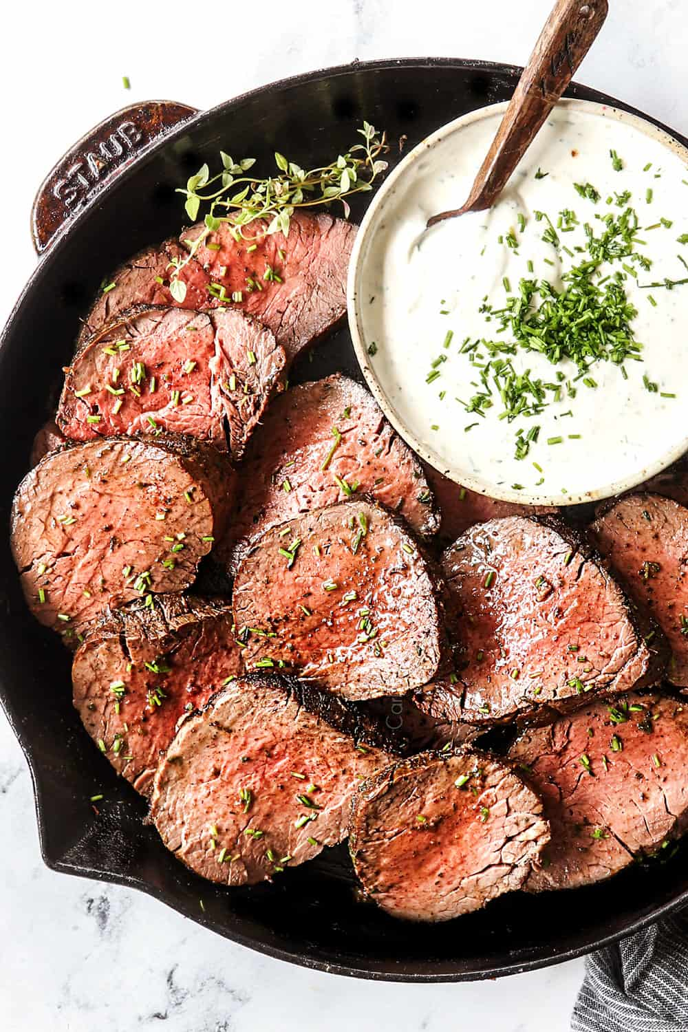 showing how to serve horseradish cream sauce by plating it with sliced beef tenderloin in a skillet