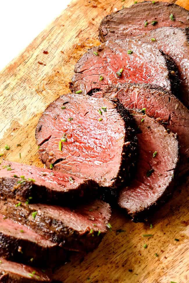 beef tenderloin recipe on a wood cutting board showing how juicy it is